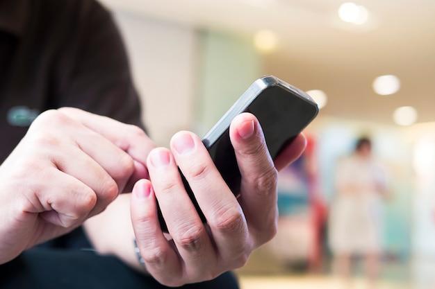 Un uomo sta usando il telefono sopra la luce vaga variopinta del bokeh nel fondo della gente e dell'ufficio
