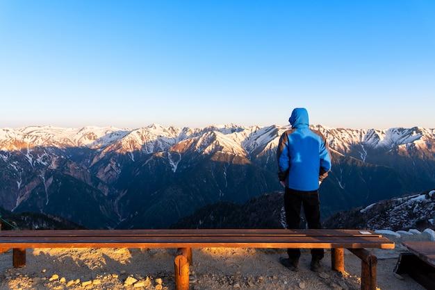 Un uomo sta vedendo lo scenario del monte tsubakuro dake al tramonto. catena montuosa di neve del parco chubu-sangaku delle alpi del nord del giappone.