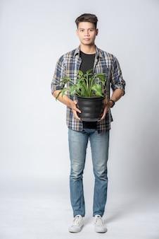Un uomo stava in piedi e teneva in mano un vaso per piante.