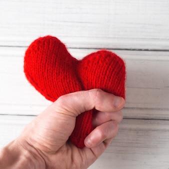Un uomo stringe le mani di un cuore rosso. concetto per il giorno di san valentino. resisti ad amare