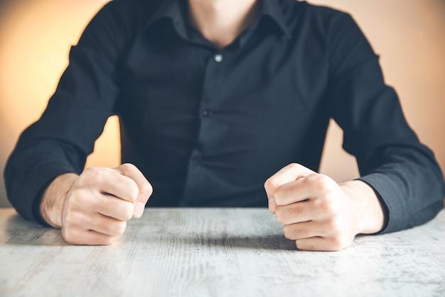 Un uomo stringeva i pugni su un tavolo di legno con rabbia