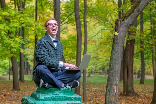 Un uomo su un piedistallo che finge di essere una statua nel parco autunnale.