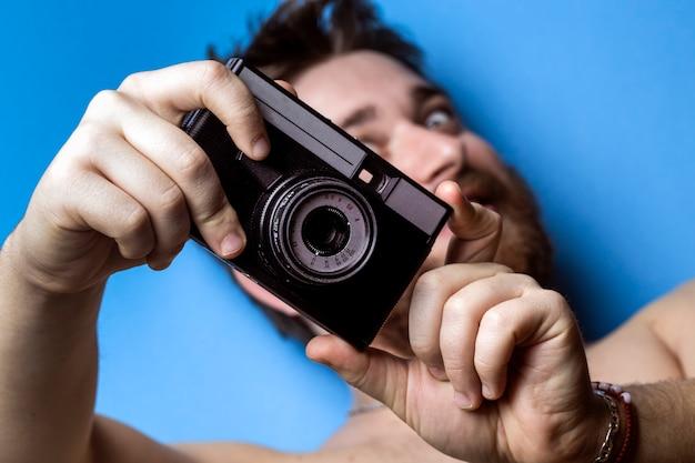 Un uomo su una superficie blu, che tiene in mano una vecchia macchina fotografica e finge di fotografare