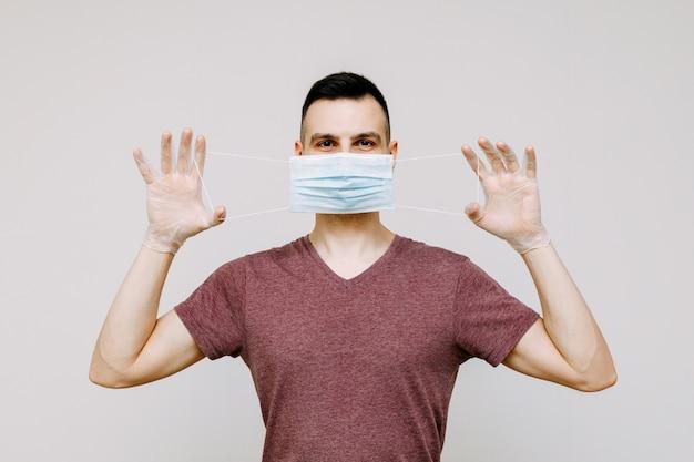 Un uomo su uno sfondo bianco indossa o rimuove una maschera igienica per prevenire l'infezione da influenza, raffreddore o coronavirus.