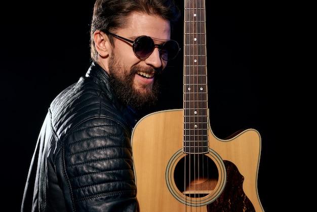 Un uomo suona la chitarra, una rock star, un musicista alla moda con una chitarra