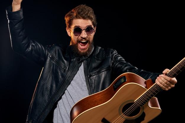 Un uomo suona la chitarra, una rockstar, un musicista alla moda con una chitarra