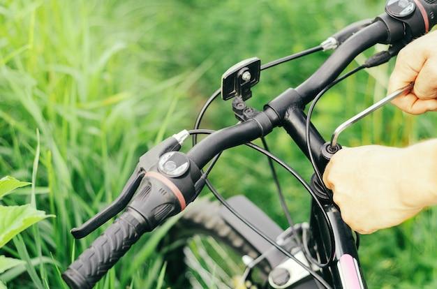 Un uomo svita i bulloni con una chiave esagonale sul manubrio di una mountain bike