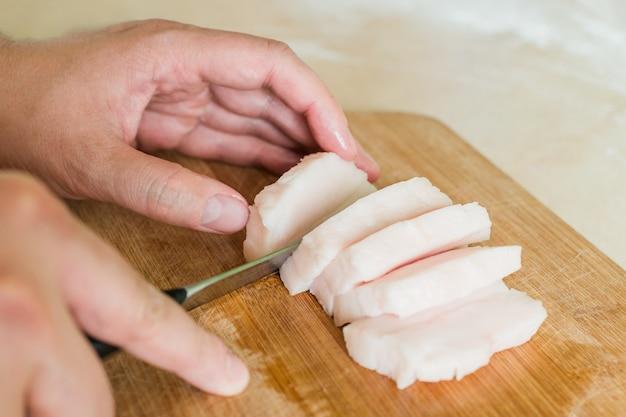 Un uomo taglia a pezzi il grasso di maiale crudo