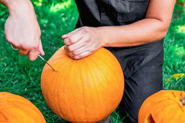 Un uomo taglia un coperchio da una zucca mentre prepara un jack-o-lantern. halloween. decorazione per la festa. avvicinamento.