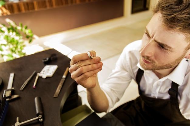 Un uomo tiene in mano un anello e lo guarda. avvicinamento