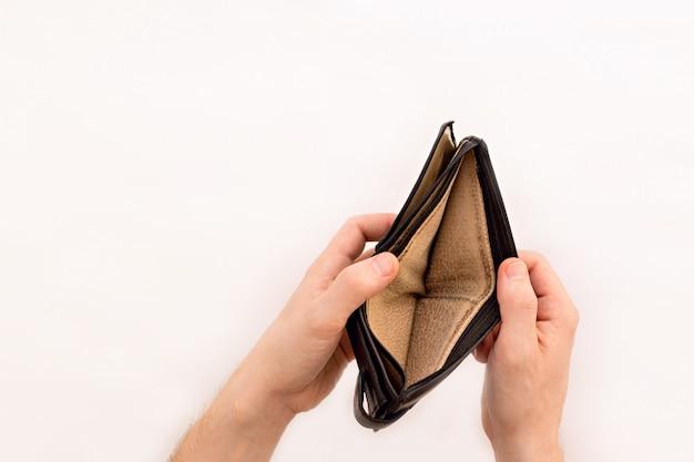 Un uomo tiene in mano un portafoglio vuoto