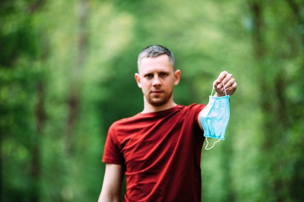 Un uomo tiene in mano una mascherina medica prima di camminare nella foresta durante il periodo di quarantena