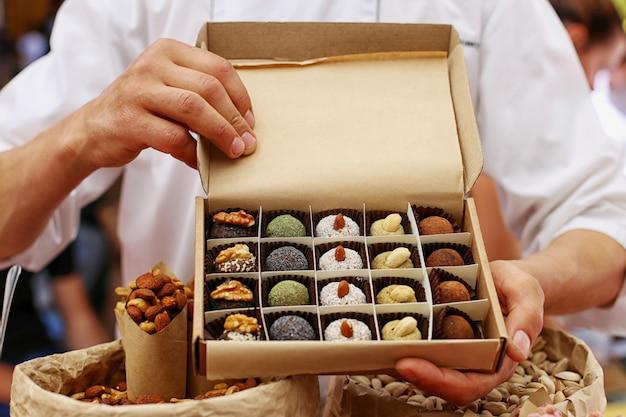 Un uomo tiene in mano una scatola di bellissime caramelle fatte a mano.