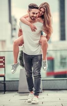 Un uomo tiene una ragazza tra le braccia per la strada
