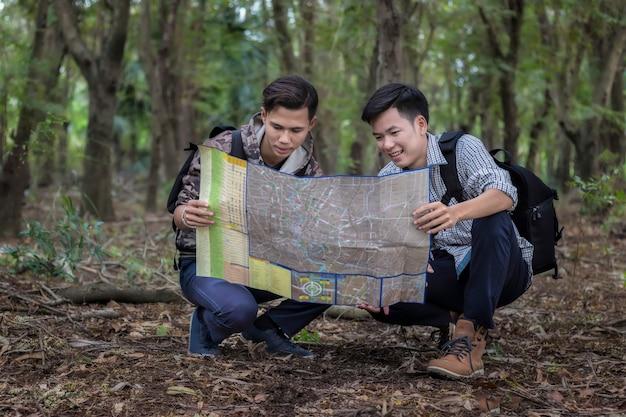 Un uomo turisti con lo zaino nella foresta guardando la cartina per imparare i sentieri escursionistici.