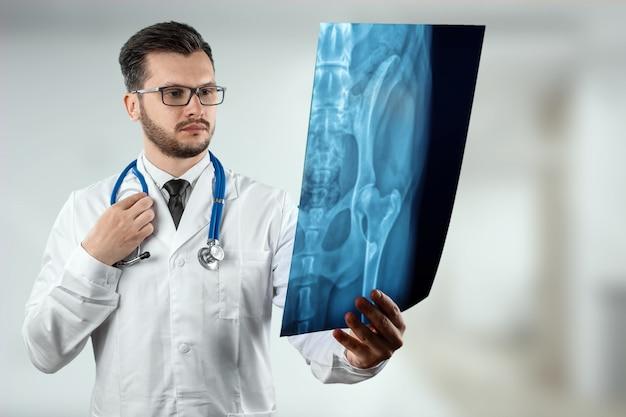 Un uomo, un dottore in camice bianco, guardando attentamente l'immagine