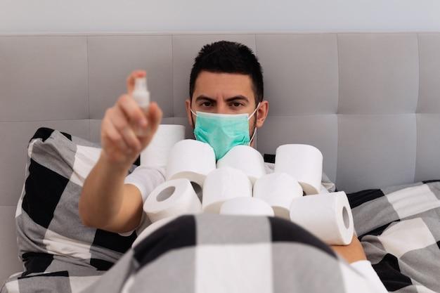Un uomo usa un disinfettante per le mani e una maschera protettiva, ha paura di ammalarsi.