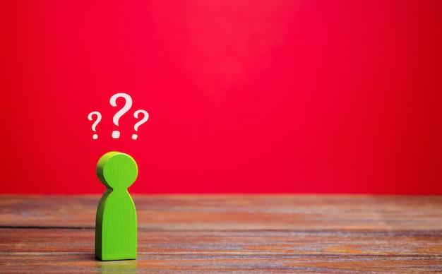 Un uomo verde in miniatura e punti interrogativi sopra di lui. incertezza