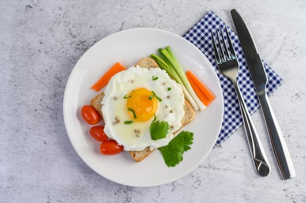 Un uovo fritto, che su un toast, condito con semi di pepe con carote e cipollotti.