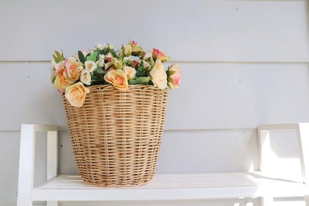 Un vaso di cesto in legno di bouquet rosa e fiori d'arancio sul tavolo in legno con parete bianca.