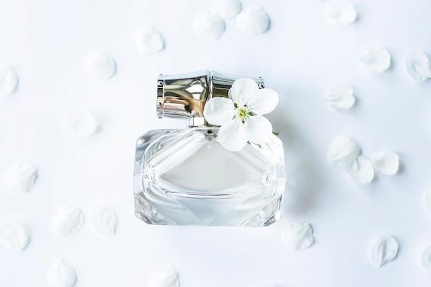Un vaso di vetro di profumo tra i petali bianchi di primavera
