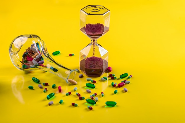 Un vaso trasparente con compresse che giace vicino a una manciata di compresse sparse di varie forme e colori accanto a una clessidra con grana rossa