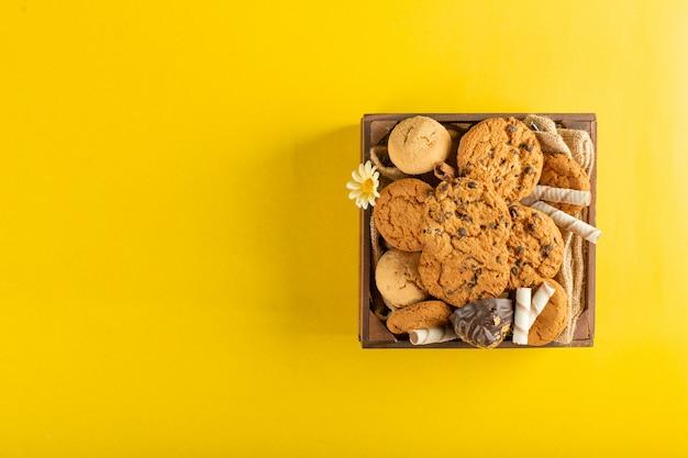 Un vassoio di legno di biscotti su giallo