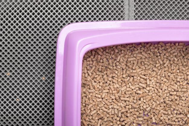 Un vassoio per gatti per una toilette con stucco ecologico in legno su un tappetino impermeabile.