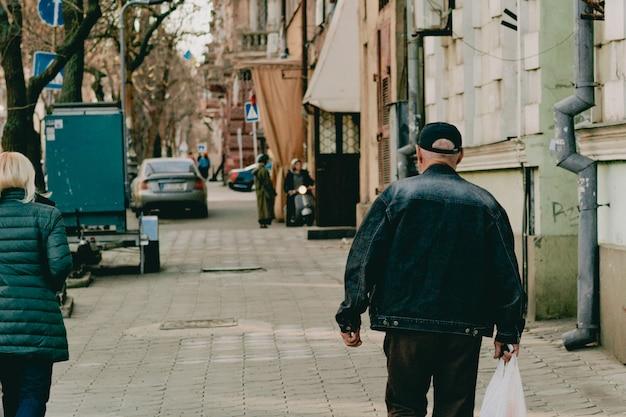 Un vecchio con berretto e giacca di jeans con un sacchetto di plastica bianco cammina per la strada della città