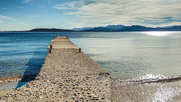 Un vecchio molo procede per alcuni metri sulle calme acque dell'isola di tavolara nei colori del mare sardo
