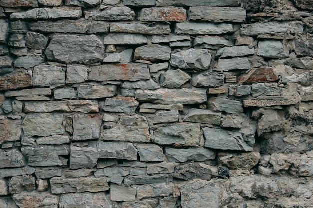 Un vecchio muro medievale in pietra, uno sfondo naturale, una replica del cosmo.