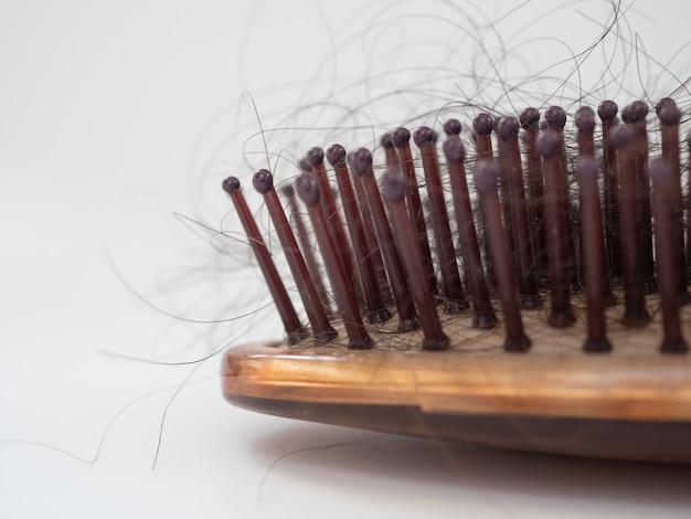 Un vecchio pettine vintage in legno sporco con perdita di capelli