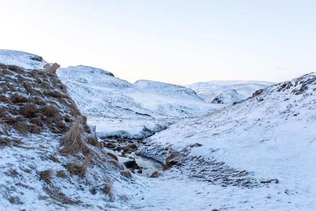 Un vecchio stabilimento balneare con una sorgente termale nelle montagne dell'islanda. paesaggio invernale islanda
