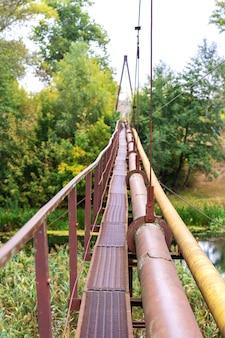 Un vecchio stretto attraversamento del fiume arrugginito, insieme a un tubo di acqua e gas. comunicazioni nel villaggio.