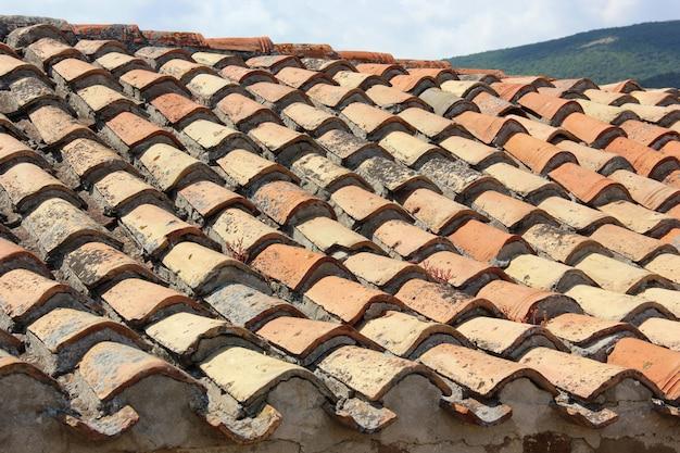 Un vecchio tetto con un rivestimento di cocci di argilla con cemento.