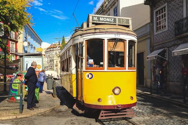 Un vecchio tram tradizionale nel centro della città di lisbona, in portogallo. la città ha mantenuto il vecchio tram tradizionale in servizio all'interno della parte storica della capitale