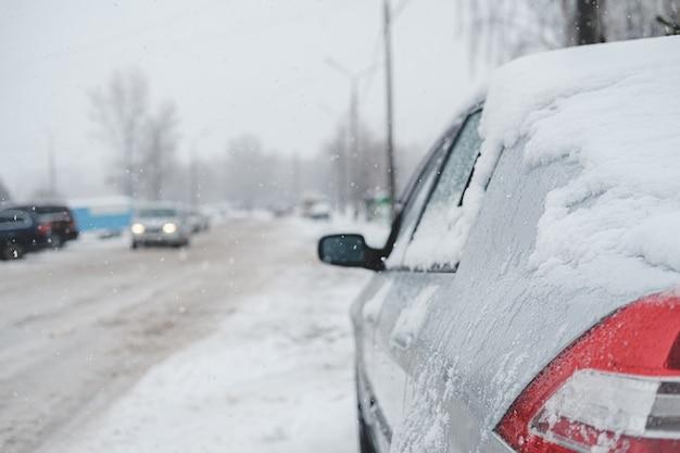 Un veicolo coperto di neve sulla strada. traffico lento nella tempesta invernale, strada piena di neve bagnata