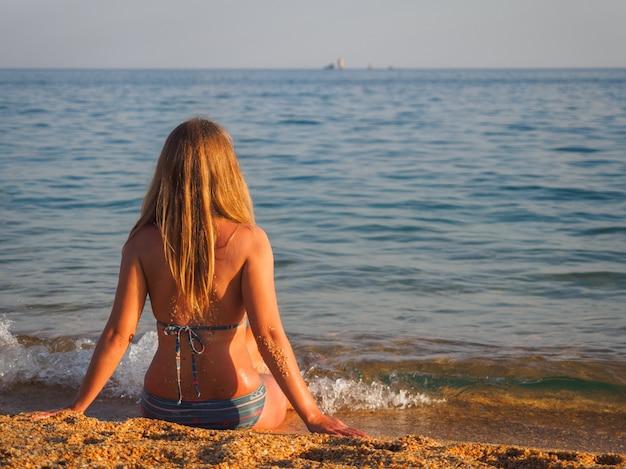 Un vestito da ragazza con la schiena rivolta a noi è seduto vicino al mare e lo guarda