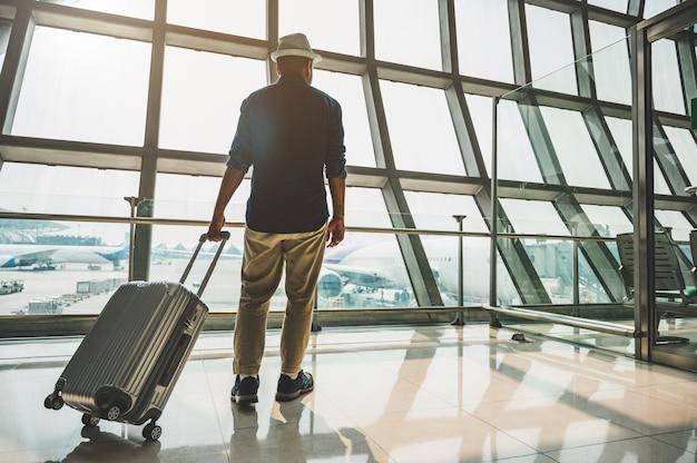Un viaggiatore di sesso maschile che indossa un cappello grigio preparazione al viaggio