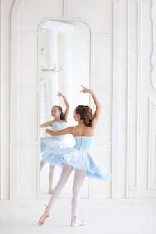 Una ballerina carina in costume da balletto e in punta di danza danza vicino allo specchio. ragazza nella classe di danza. la ragazza studia balletto. la ballerina sta ballando. la ballerina si sta allenando allo specchio.
