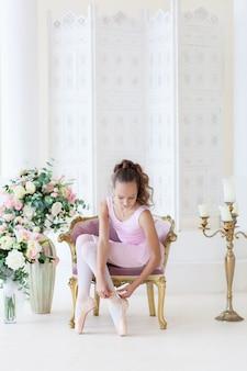 Una ballerina carina in un costume da balletto rosa è seduta su una sedia, legando scarpe da punta.