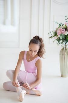 Una ballerina carina in un costume da balletto rosa è seduta sul pavimento e sta legando scarpe da punta. ballerina nella classe di danza. la ragazza studia balletto.