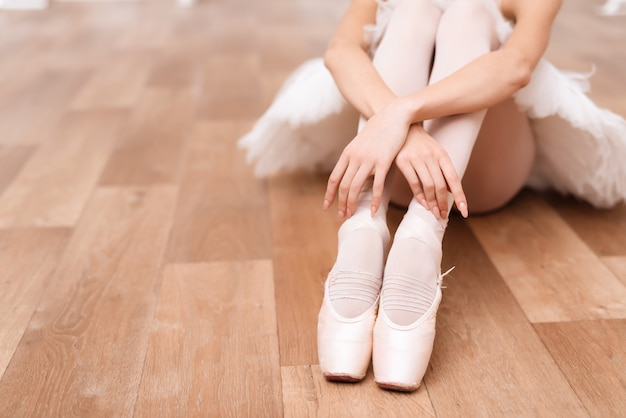 Una ballerina professionista è seduta sul pavimento.