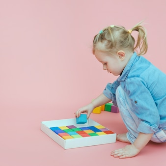 Una bambina affascinante in abiti di jeans su uno sfondo rosa