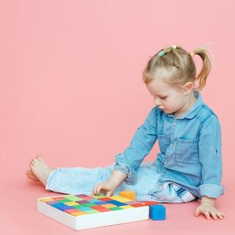 Una bambina affascinante in abiti in denim su uno sfondo rosa mette in legno cubi multicolori in una scatola bianca.