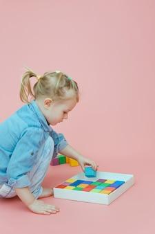 Una bambina affascinante in abiti in denim su uno sfondo rosa