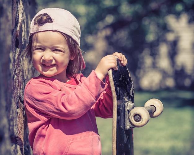 Una bambina alla moda tiene in mano uno skateboard e gioca fuori, le belle emozioni di un bambino.