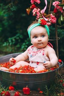 Una bambina bagna in una bacinella con fragole nel giardino.