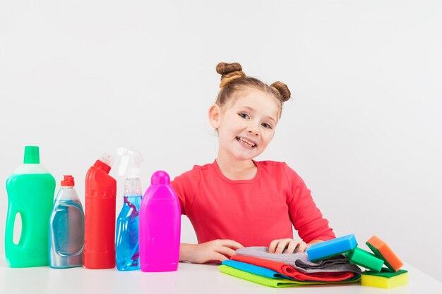 Una bambina carina con prodotti per la pulizia
