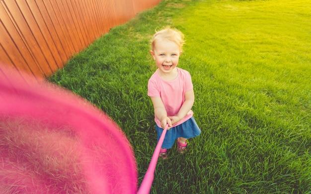Una bambina carina con una maglietta rosa e una gonna di jeans corre intorno al campo e cattura farfalle